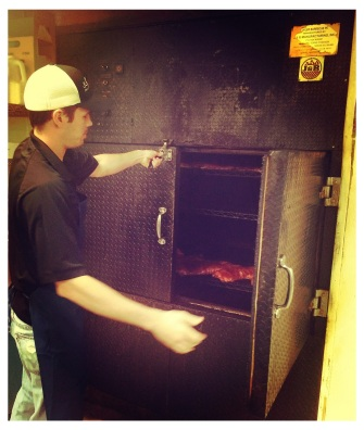 Assistant Pit Master, Taylor, checking on the meat in the rotisserie style Oyler barbecue pit.