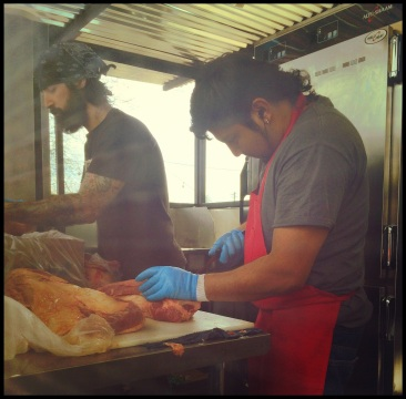 La Barbecue employees expertly applying the dry rub before going on the smoker.