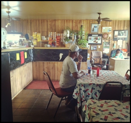 A lone patron sits at a table with Mama B sitting in the corner smoking her cigarettes.
