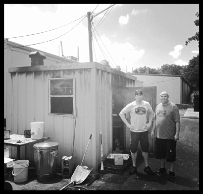 Shawn Eagle and Cody Smithers stand beside the smokehouse out behind the restaurant.